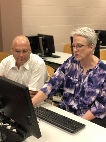 Instructional Designer Carey Hamburg works with Penny Antley during a recent Tech Time.